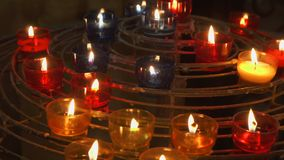Candles burning in catholic church. Festive glow in cathedral. Holy place illuminated by flames stock footage