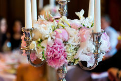 Candles burning in a chandelier on elegant dinner table Stock Photo