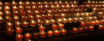 Candles burning in church. Many red tealights burning in church Royalty Free Stock Photos