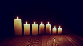 Candles burning in dark. Candles standing in line burning in dark fluttering on wind, toned zoom in video stock video