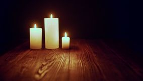 Candles burning in dark. Three candles burning in dark fluttering on wind, toned zoom in rack focus video stock video footage