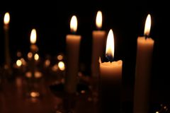 Candles burning in darkness. Close up of candles burning in darkness Royalty Free Stock Photo