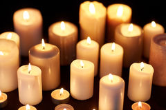 Candles burning in darkness over black background Royalty Free Stock Photos