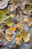 Candles burning between dry leaves Stock Photo