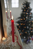 Candles Burning On Mantelpiece On Christmas Day. Closeup of candles burning on mantelpiece with Christmas tree in background Royalty Free Stock Image
