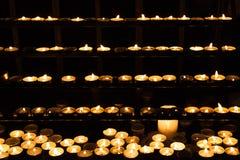 Candles burning on shelves in dark church Stock Photos