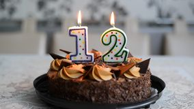 Candles on cake in form of figures twelve stock footage