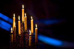 Candles in a candelabra. A set of candles lit in a candelabra on a black background Stock Images