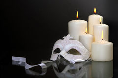 Candles and carnival mask over black background Stock Photography