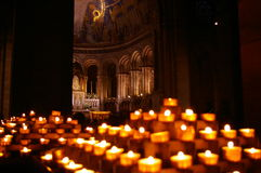 Candles in cathedral. Votive candles illuminate the entry to a cathedral Stock Photos