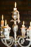 Candles in a chandelier. With some melted wax forming stalactites Stock Photo