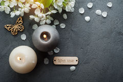 Candles and cherry flower on concrete background Royalty Free Stock Photo