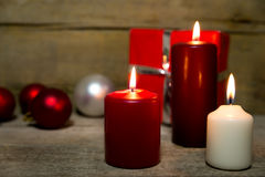 Candles, christmas balls and a red gift on wooden table Stock Photography