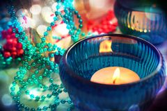 Candle in a turquoise candlestick on the background of Christmas lights and bokeh effect tinsel stock image