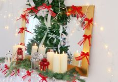 Candles and Christmas decorations on mantelpiece. In room Royalty Free Stock Photography