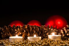 Candles with christmas pine cone in atmospheric light Stock Photography
