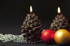Candles with christmas-tree decorations. Two candles as a knop with christmas-tree decorations on black background Stock Photos