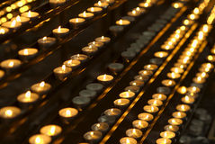 Candles in a church. Rows of burning candles in a catholic church Royalty Free Stock Images