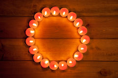 Candles cirlce shape on warm golden wood. Candles glowing in circle shape on golden wood background Royalty Free Stock Image