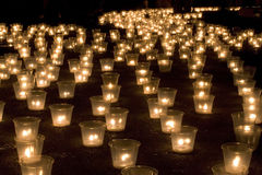 Candles in the dark. Candles in plastic cups outside Stock Photography