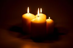 Candles in the dark. Four candles of different sizes burning in the dark Royalty Free Stock Images