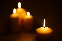 Candles in the dark. Four candles of different sizes burning in the dark Royalty Free Stock Image