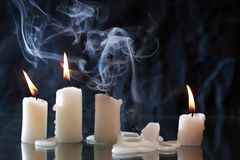 Candles On Dark. Set of lighting candles with fire and smoke on nice dark background royalty free stock photography