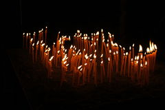 Many thin candles glowing in the darkness. Thin candles lightening in the darkness, spiritual glowing in monastery, composition of candles Royalty Free Stock Image