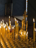 Candles for the dead. Lighting candles for the dead before the crucifixion of Christ in orthodox temple. Commemoration of dead concept. Selective focus on royalty free stock image