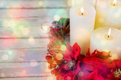 Candles decorated with flowers nest basket on wooden plank Royalty Free Stock Images