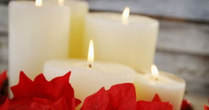 Candles decorated with flowers on wooden plank stock video