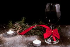 Candles and decorated wine glass for New Year on wooden desk and snow stock photo
