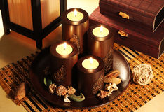 Candles decorative. Composition of four decorative candlesticks in the Japanese style on a background of bamboo caskets Royalty Free Stock Image