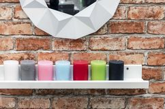 Candles of different colors are on the white shelf in the loft interior.  stock photo