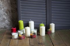 Candles of different flowers and forms stand on a floor near stock photography