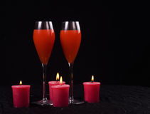 Candles and drinks. Closeup of two full flute glasses with lighted red candles, isolated on black background Stock Image