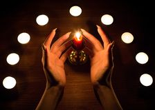 Candles and female hands with sharp nails. Divination and witchcraft, low key. royalty free stock photos