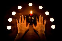 Candles and female hands with sharp nails on wooden surface. Divination and witchcraft, low key. royalty free stock photography