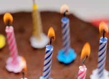 Candles on a festive cake. On a light background Stock Photo