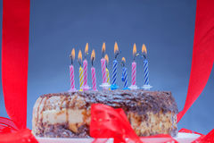 Candles on a festive cake. On a light background Stock Images