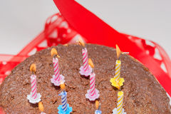 Candles on a festive cake. On a light background Royalty Free Stock Photo