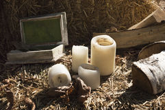Candles, firewood and wooden box lying on straw Stock Image