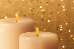 Candles with flame on golden bokeh Stock Photos