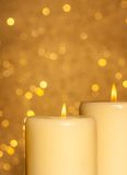 Candles with flame on golden bokeh Royalty Free Stock Photography