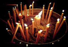 Candles flame light cutting though the darkness Stock Images