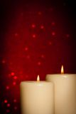 Candles with flame and space for text on red bokeh Stock Image