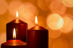 Candles with flames at reflective advent season. With lights as bokeh Stock Images