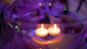 Candles floating in a glass vase in the evening on a violet background lighting stock footage