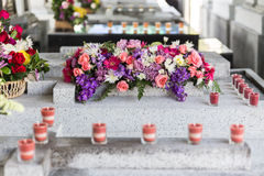 Candles and Flowers over Grave in The Annual Blessing of Graves at Ratchaburi Province, Thailand Stock Photo