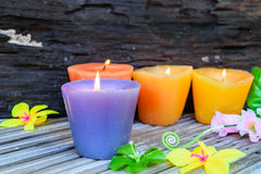 Candles and flowers plastic beautiful. On bamboo table on old wood background Royalty Free Stock Photography